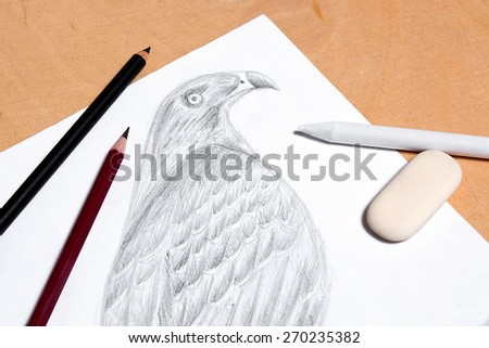 Graphite pencil, eraser and stamp with drawing hawk on the wooden background.  #270235382