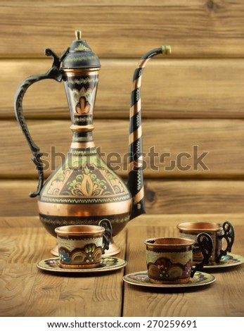 Traditional Turkish tea set: vintage painted copper cups with teapot on wooden table