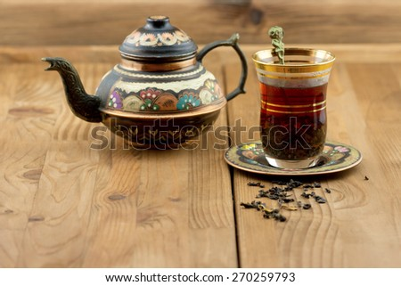 Traditional Turkish tea set: vintage glass cup with teapot and dry tea leaves on wooden table