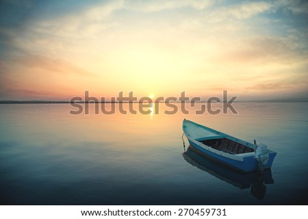 Canoe floating on the calm water under amazing sunset Royalty-Free Stock Photo #270459731