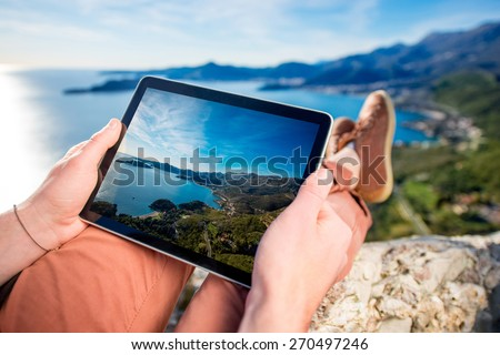 Man holding digital tablet on the mountain top on the sea scape background #270497246
