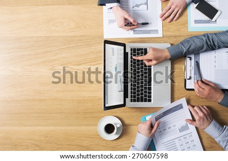 Business team hands at work with financial reports and a laptop, blank copy-space on left, top view Royalty-Free Stock Photo #270607598