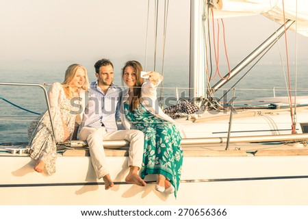 Young people taking selfie on exclusive luxury sailing boat - Concept of friendship and travel with best friends using modern smartphone as new trends and technology - Warm sunset color tones