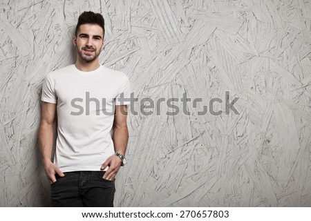 Smiling man in white blank t-shirt, and OSB wooden wall background #270657803