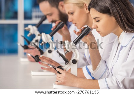Science team working with microscopes in a laboratory. #270761135