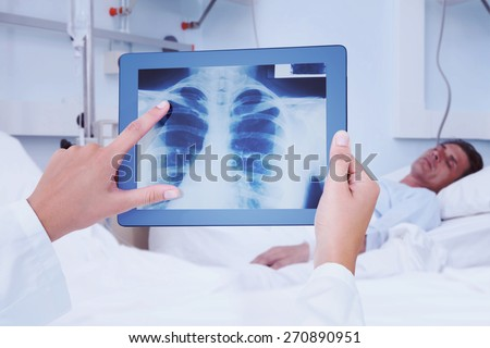 Composite image of doctor looking at xray on tablet #270890951