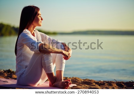 Tranquil young woman sitting on the beach Royalty-Free Stock Photo #270894053