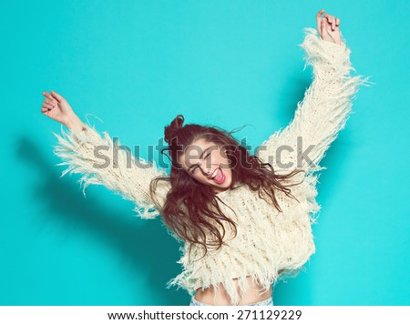 cheerful fashion girl going crazy making funny face and dancing. Blue color background. hipster style