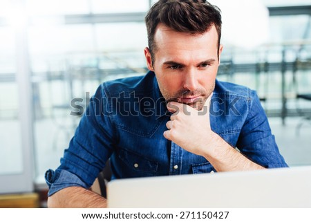 Young focused architect working on a laptop Royalty-Free Stock Photo #271150427
