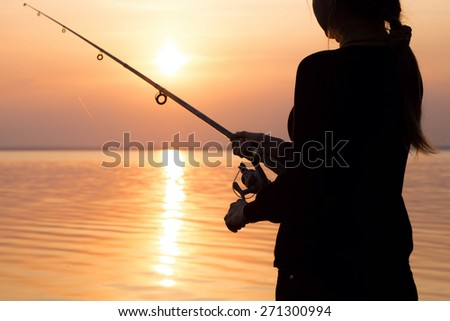 young girl fishing at sunset near the sea #271300994