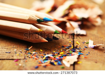 Wooden colorful pencils with sharpening shavings, on wooden table Royalty-Free Stock Photo #271387073