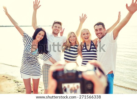 summer, sea, tourism, technology and people concept - group of smiling friends with camera on beach waving hands and photographing #271566338