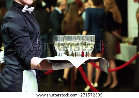 catering or celebration concept. Waiter holding a tray with glasses of vine at party Royalty-Free Stock Photo #271572305