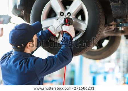 Mechanician changing car wheel in auto repair shop Royalty-Free Stock Photo #271586231