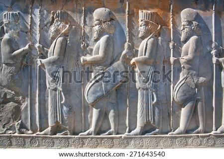 Soldiers of historical empire with weapon in hands. Stone bas-relief in ancient city Persepolis, Iran. Capital of the Achaemenid Empire (550 - 330 BC). UNESCO declared Persepolis a World Heritage Site #271643540