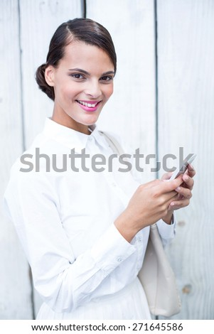 Pretty woman using her smartphone in front of wooden grey planks #271645586