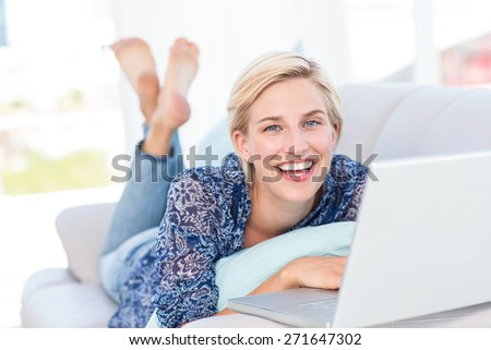 Pretty blonde woman lying on the couch and using her laptop in the living room. Working from home in quarantine lockdown. Social distancing Self Isolation #271647302