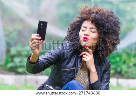 exotic beautiful young girl with dark curly hair taking selfie with her cell phone sitting in the garden