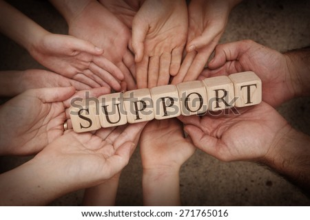 Team Holding Building Blocks Spelling out Support Royalty-Free Stock Photo #271765016