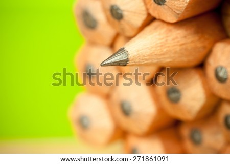 Macro image of graphite tip of a sharp ordinary wooden pencil as drawing and drafting tool, standing among other pencils, symbolizing individuality approach and concept as standing out from the crowd