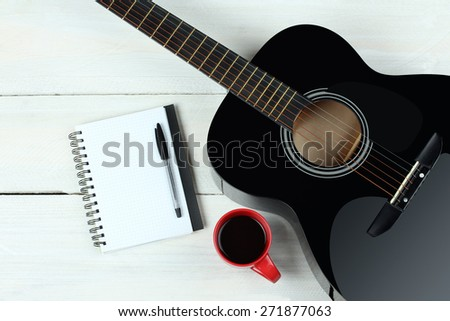 Acoustic guitars with a notebook and a cup of coffee on wood background