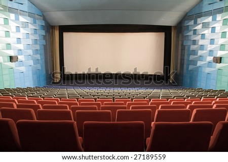Empty cinema auditorium with line of chairs and stage with silver screen. Ready for adding your own picture. #27189559
