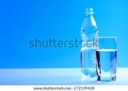 Bottle ang glass of water on blue background #272139428