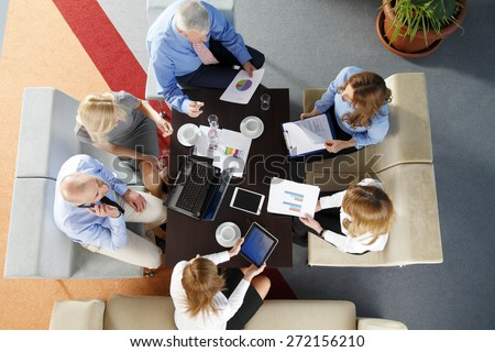 Image from above of business people sitting around the desk and working on presentation. Teamwork at office.  #272156210