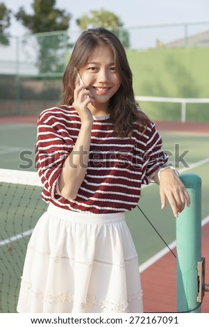 portrait of young beautiful asian woman talking smartphone in tennis course sport field use for modern life and digital telecommunication technology #272167091