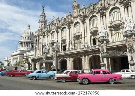 Row of brightly colored vintage American cars stand parked on the street in front of the Galician Palace on Prado Street in central Havana Cuba  #272176958