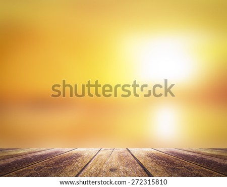 Summer holiday concept: Wooden table border with blurry beautiful sunlight and golden sunset background