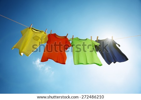 T-shirts hanging on a clothesline in front of blue sky and sun #272486210