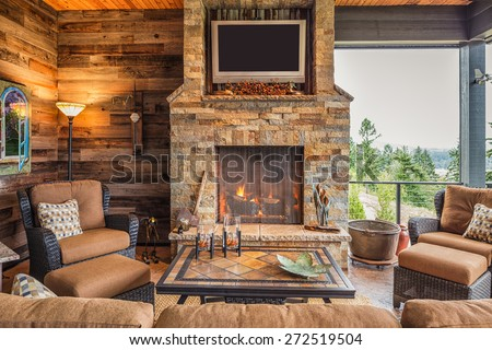 Covered Outdoor Patio Outside New Home with Couch, Chairs, TV, Fireplace, and Roaring Fire #272519504