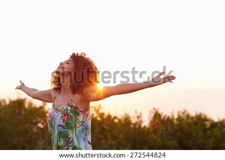Beautiful mixed race woman expressing freedom outdoors with her arms outstretched Royalty-Free Stock Photo #272544824