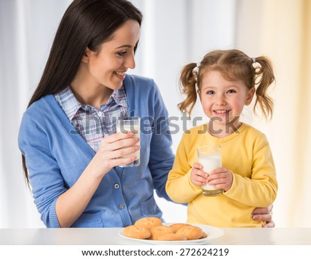 Adorable girl is having an healthy snack with cookies and milk with her mother. #272624219