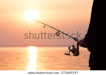 young girl fishing at sunset near the sea #272669297