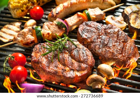 Assorted delicious grilled meat with vegetables over the coals on a barbecue Royalty-Free Stock Photo #272736689
