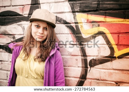Blond stylish teenage girl stands near urban wall with graffiti, photo with warm retro tonal correction effect, instagram old style filter #272784563
