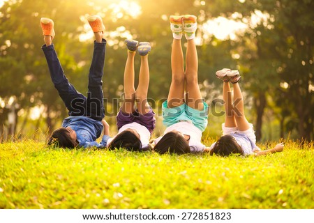 Group of happy children lying on green grass outdoors in spring park Royalty-Free Stock Photo #272851823