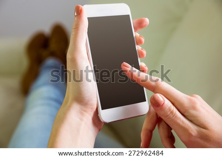 Casual woman using her smartphone at home in the living room #272962484