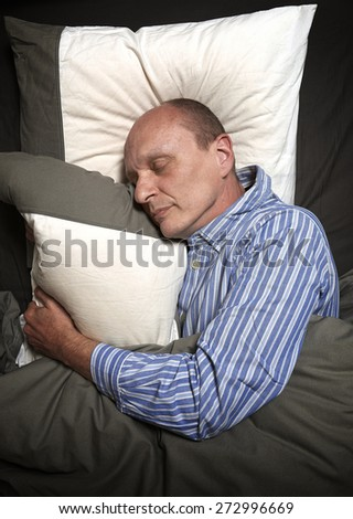 Man in pajamas or jammies sleeping in bed #272996669