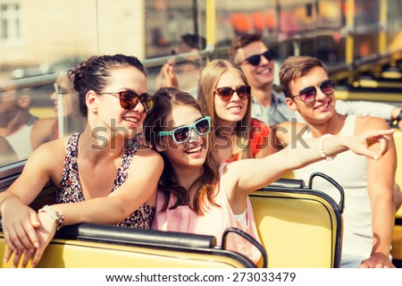 friendship, travel, vacation, summer and people concept - group of smiling friends traveling by tour bus Royalty-Free Stock Photo #273033479