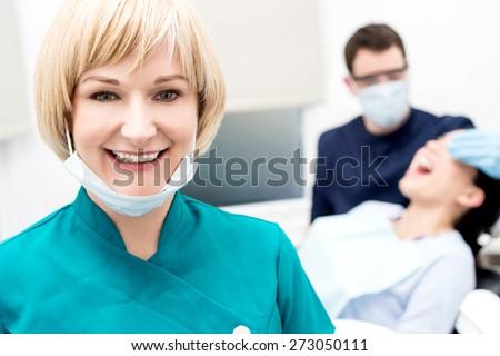 Female dental assistant removing her face mask #273050111