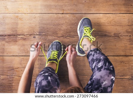 Unrecognizable young runner tying her shoelaces. Studio shot on wooden floor background. Royalty-Free Stock Photo #273097466