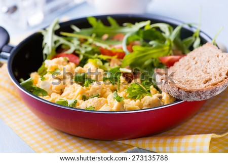 Scrambled eggs with fresh tomato and arugula salad in frying pan, selective focus #273135788