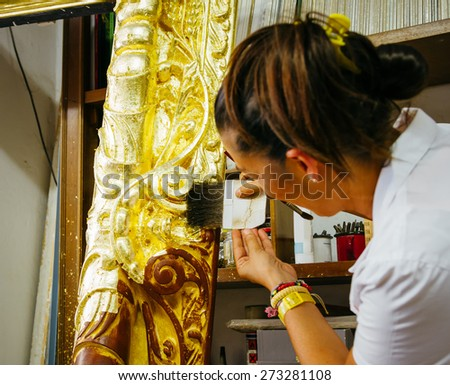 Female artisan decorating a big wooden picture frame.Application of gold leaf. Focus on the tool. Lomo effect.