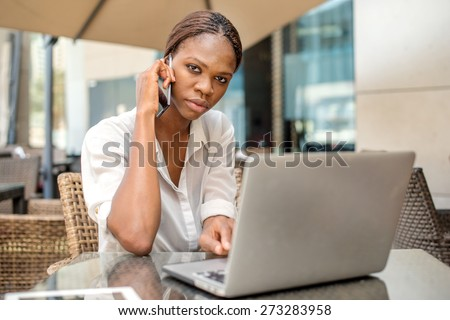 Business conversation with a client in Dubai. African businesswoman businessman holding a cell phone and talking to a customer at a cafe table in Dubai downtown with a laptop #273283958