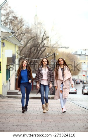 Three young beautiful girlfriends in autumn clothes walking down the street #273324110