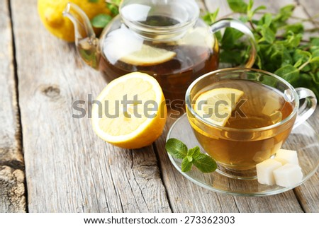 Cup of tea with mint and lemon on grey wooden background #273362303