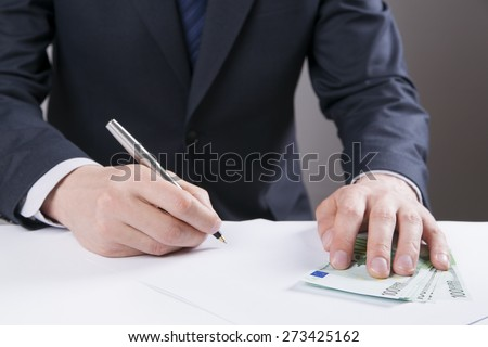 Concept - corruption. Giving a bribe. Money in hand. Sign the document. #273425162